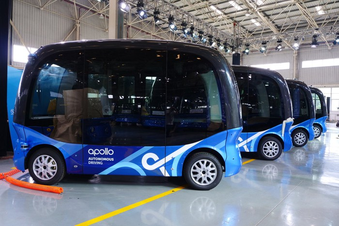 Several of Baidu's Apolong self-driving minibuses parked in large warehouse.