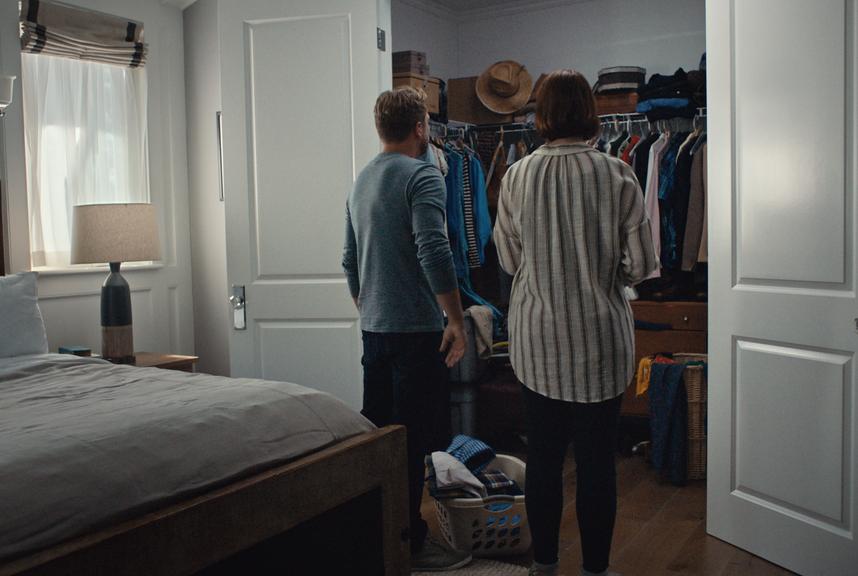 A couple looks into a messy closet.