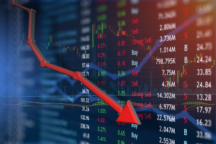 Line with red arrow indicating losses, with stock market prices on a colorful display in the background