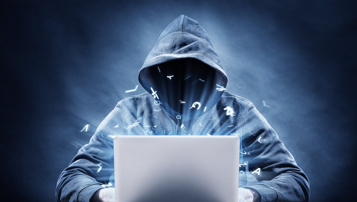 Hooded figure in front of a laptop
