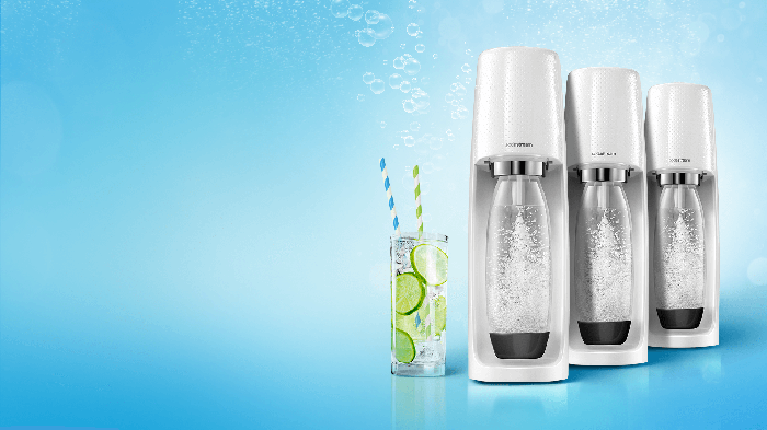 Three SodaStream water makers next to a glass of water with lime and two straws.