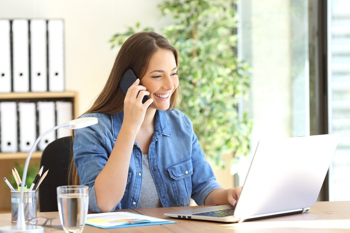 A smiling woman on her cell phone sits at a desk and looks at a laptop.