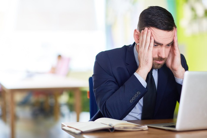 Man in business suit holding his head as if frustrated while looking at laptop