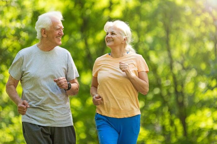 Smiling senior couple out for a jog.