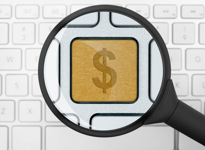 Magnifying glass taking a closer look at a golden dollar-sign key in the middle of an otherwise plain, white computer keyboard.