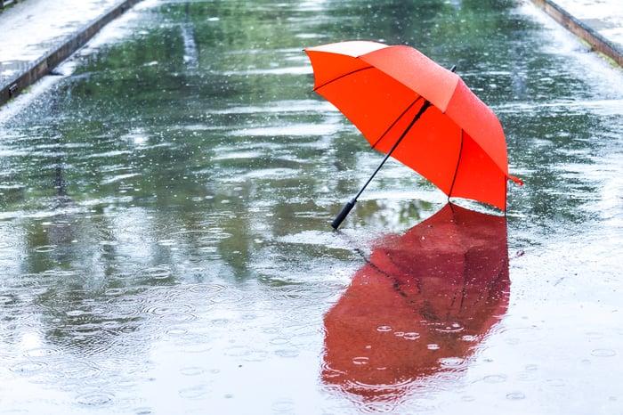 Rain falling on a red umbrella on an empty street