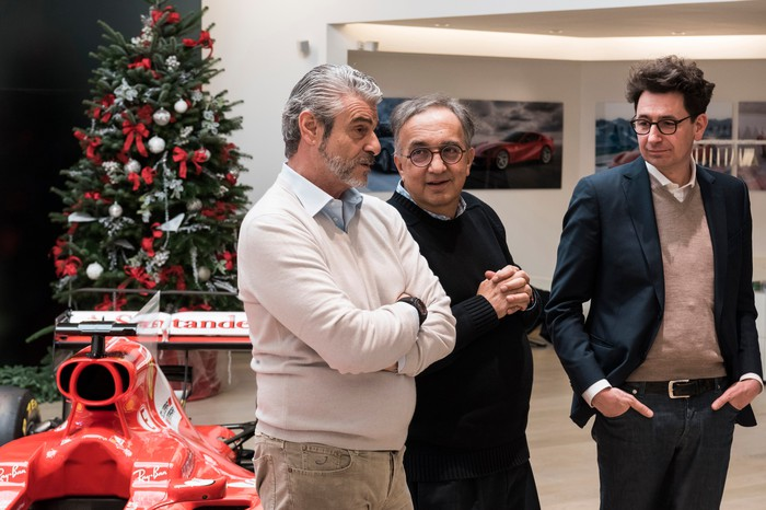 Marchionne is shown with two executives from Ferrari's racing team, at an event in December of 2017. A Ferrari Formula 1 race car and a Christmas tree are visible in the background.