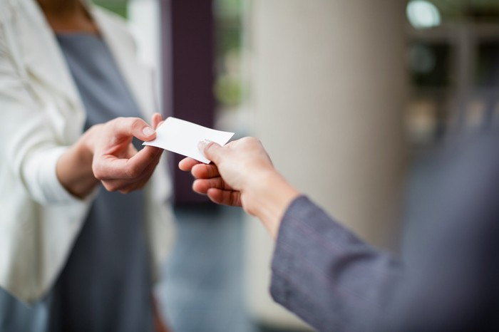 Woman giving another her business card.