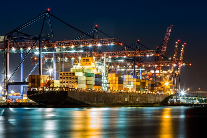 A container ship in a port at night.