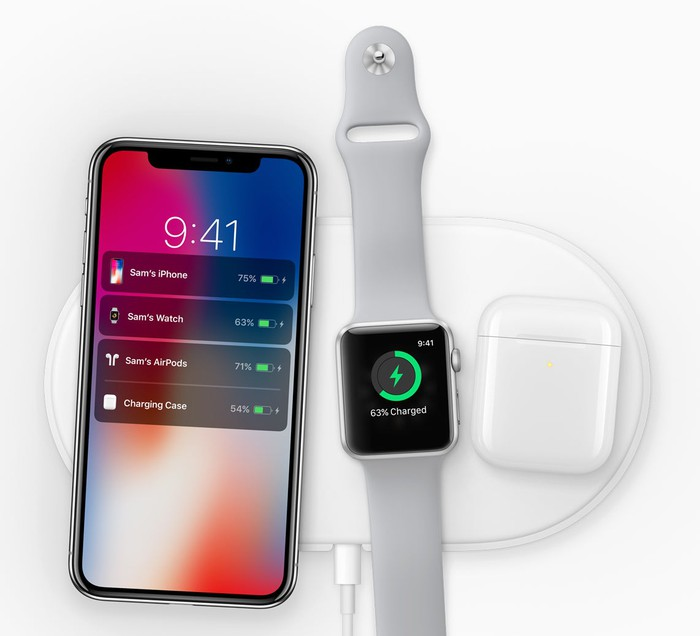 An iPhone, Apple Watch, and AirPods laying on a charging pad.