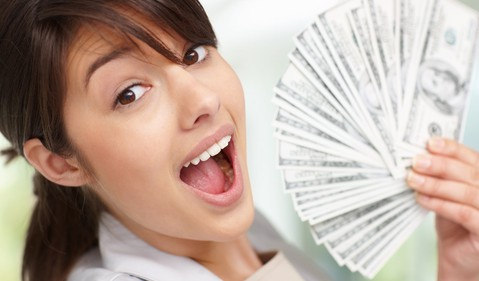 Young Woman Fanning Cash Surprised Dividend Getty