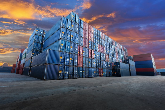 Stacks of blue and red stacked industrial containers at dusk.