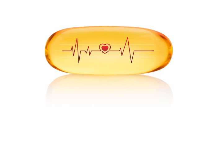 A fish oil pill with a heart icon label in the middle. The pill is set against a white background.