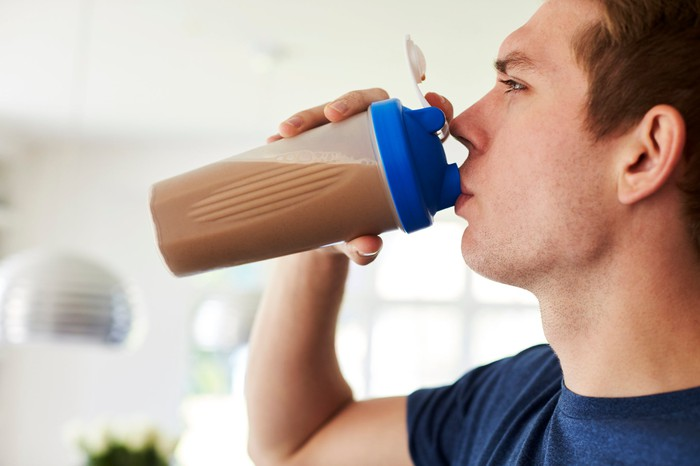 Man drinking a protein or nutritional shake.