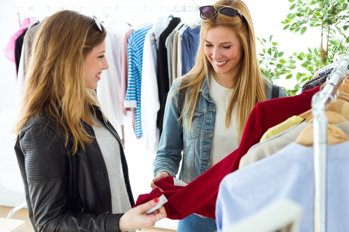 Two women looking at clothes on a rack