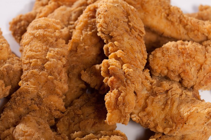 A close-up shot of a plate of fried chicken strips.