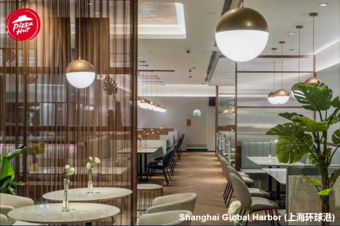 The interior of the new Shanghai Pizza Hut. Chairs and walls are in neutral white with soft neutral brown accents and modern lighting.