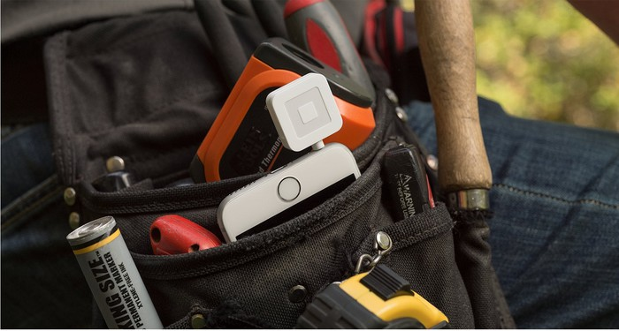 Square card reader attached to smartphone in a toolbelt.