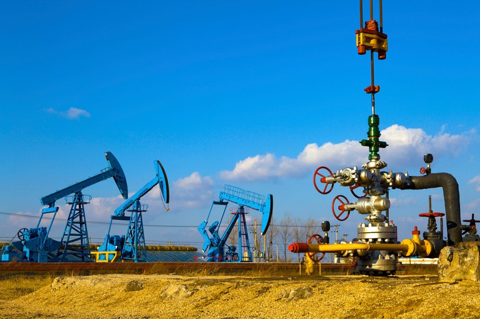A close-up of a natural gas wellhead with three oil pumps in the background.