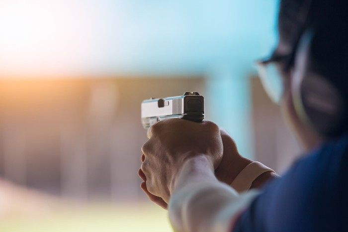 A person firing a pistol at a shooting range.