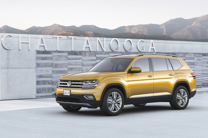 A yellow VW Atlas, a midsize seven-passenger SUV, shown parked in front of a city sign in Chattanooga, Tennessee