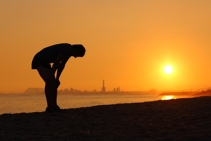 Silhouette of a tired sportsman resting with his hands on his knees in front of a golden Spanish sunset.