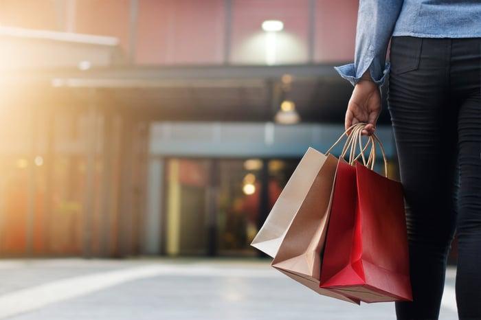 Shopper holding bags, walking toward mall entrance.