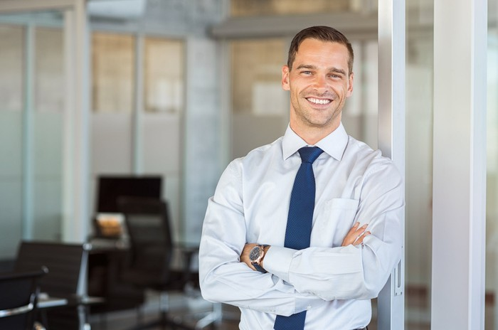 Smiling professionally dressed man, standing in an office setting.