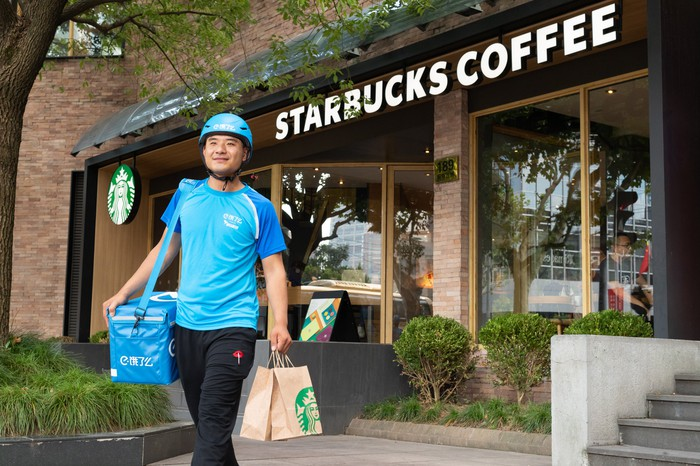Alibaba employee in a blue uniform walks out of Starbucks with a customer delivery in a bag