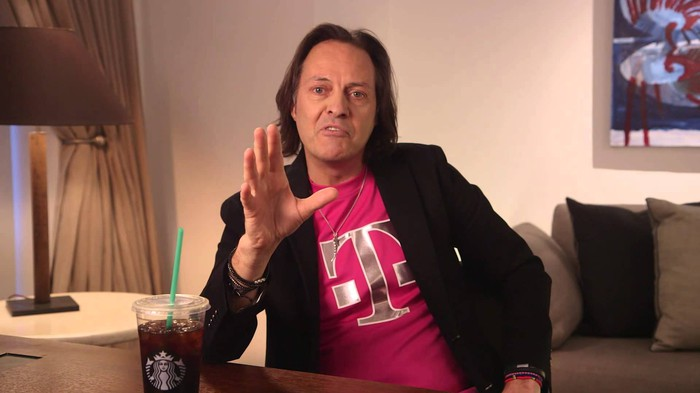 T-Mobile US CEO John Legere sitting at a table