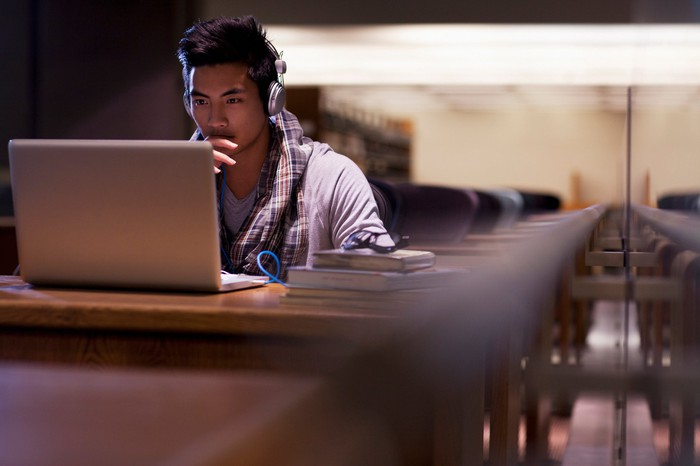 Student on laptop in a quiet room with rows of desks
