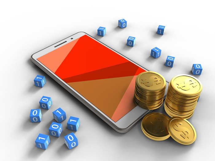 A mobile phone surrounded by coins and dice.