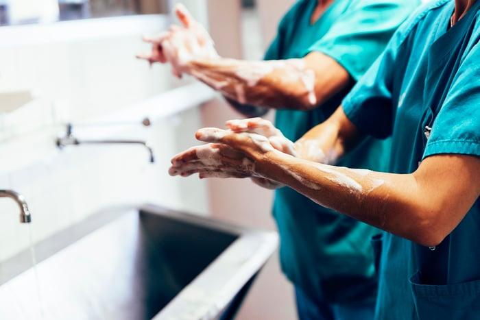 SUrgeons in green scrubs washing hands