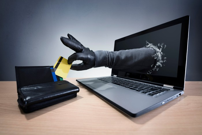 A black-gloved hand reaches out from a laptop screen to steal a credit card from a nearby wallet.