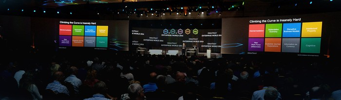 Conference hall with OpenText presentation given by speakers at front of hall, in front of digital screens.