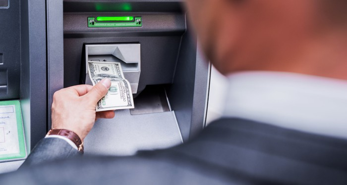 A person inserting a $100 bill into an ATM machine.