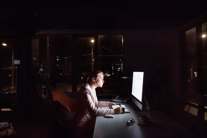 Woman sitting in front of a computer at night.