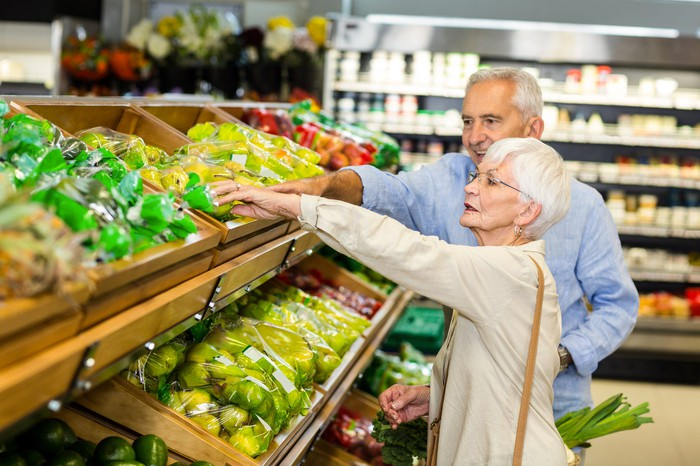 Senior couple at a supermarket, reaching for fruit in a bin.