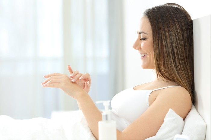 A woman rubs skin cream on her hands.
