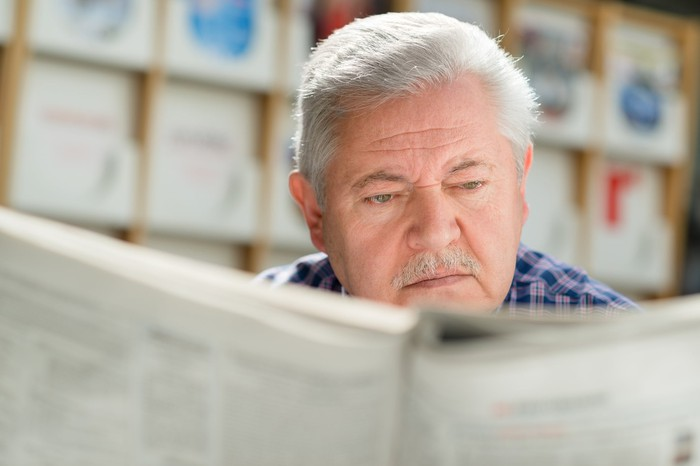 Older man reading a newspaper