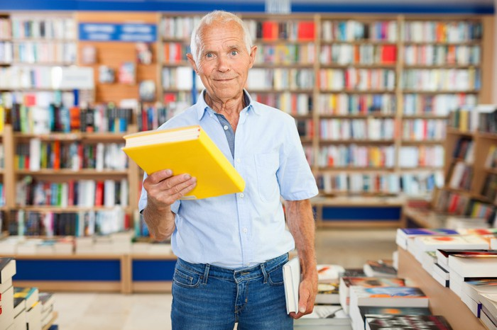 An older man holds up a book in a bookstore