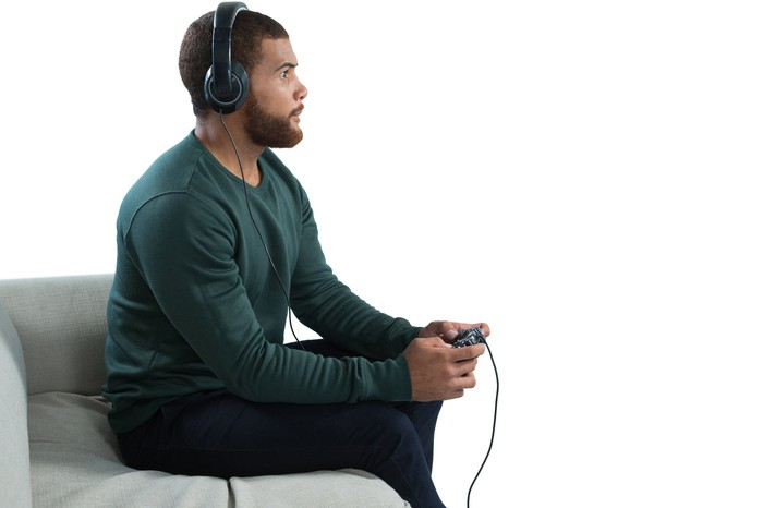 Gamer sitting on a couch, wearing a headset and holding a gaming console controller.