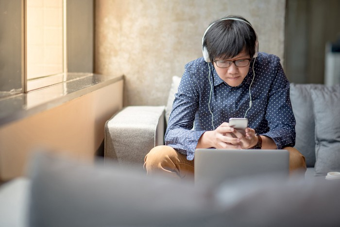 A boy wearing headphones sitting in a chair and using a smartphone.