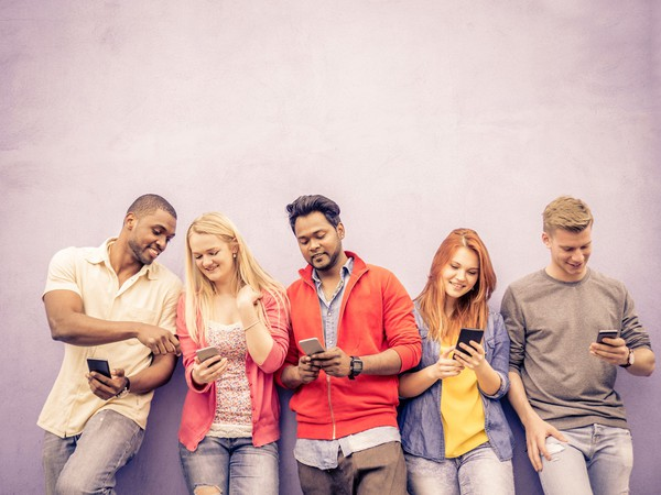 FIve adults leaning on a wall with smartphones in their hands