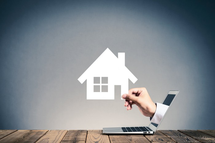 A hand emerging from a laptop holding a house.