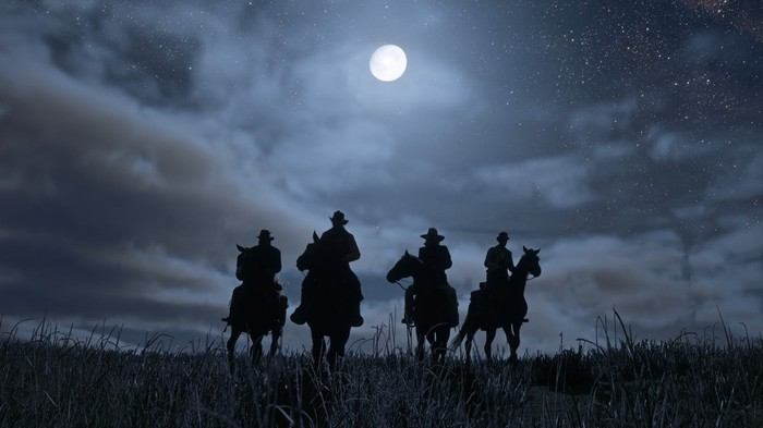 Four cowboys on horseback riding the plains silhouetted by a full moon, in a scene from Red Dead Redemption 2.
