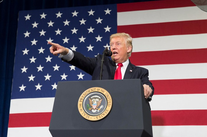 President Trump addressing and pointing to an audience, with the American flag in the background.