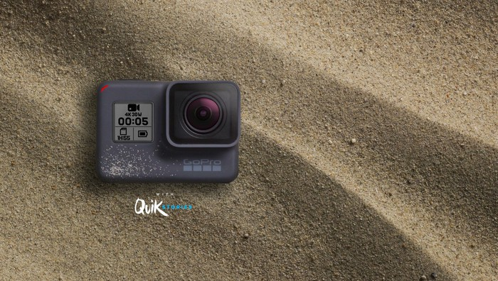 GoPro Hero5 Black camera sitting in sand.