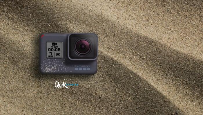 GoPro Hero5 Black camera sitting in sand.
