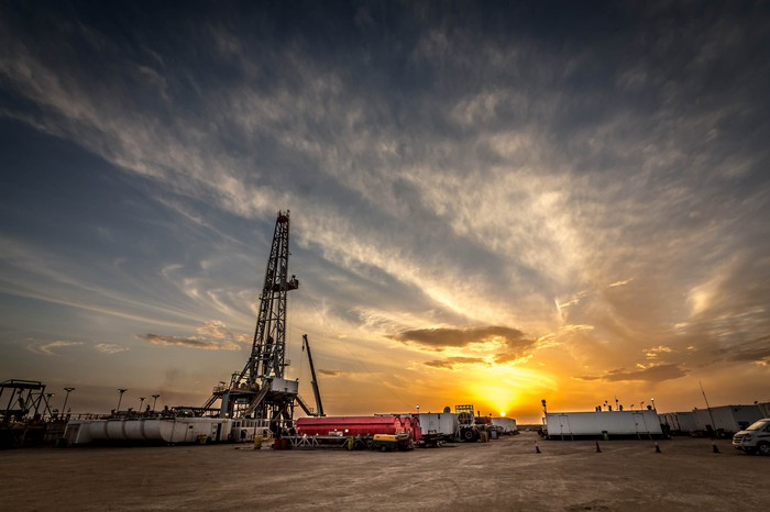A drilling rig site with the sun setting in the background.